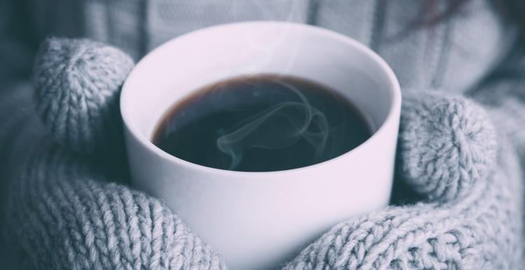Person holding a hot cup of coffee wearing woolly gloves