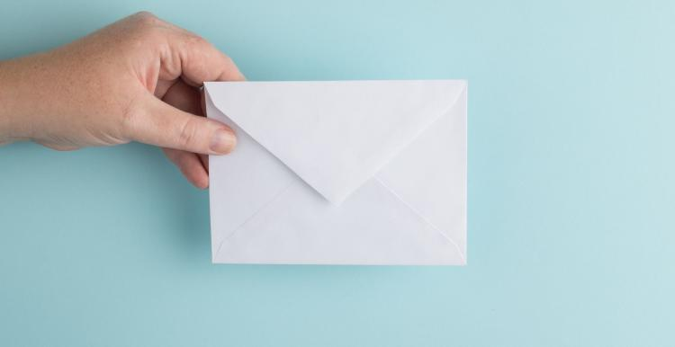 hand holding envelope on blue background