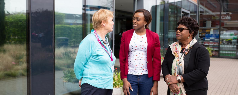 Three women standing outside a hospital talking