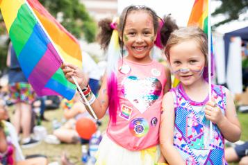 two young girls at pride with rainbow flags