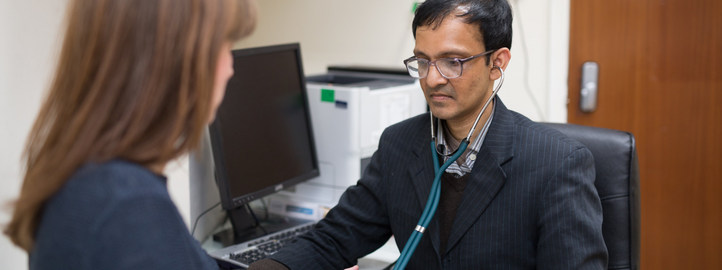 Male doctor checking pressure of female patient