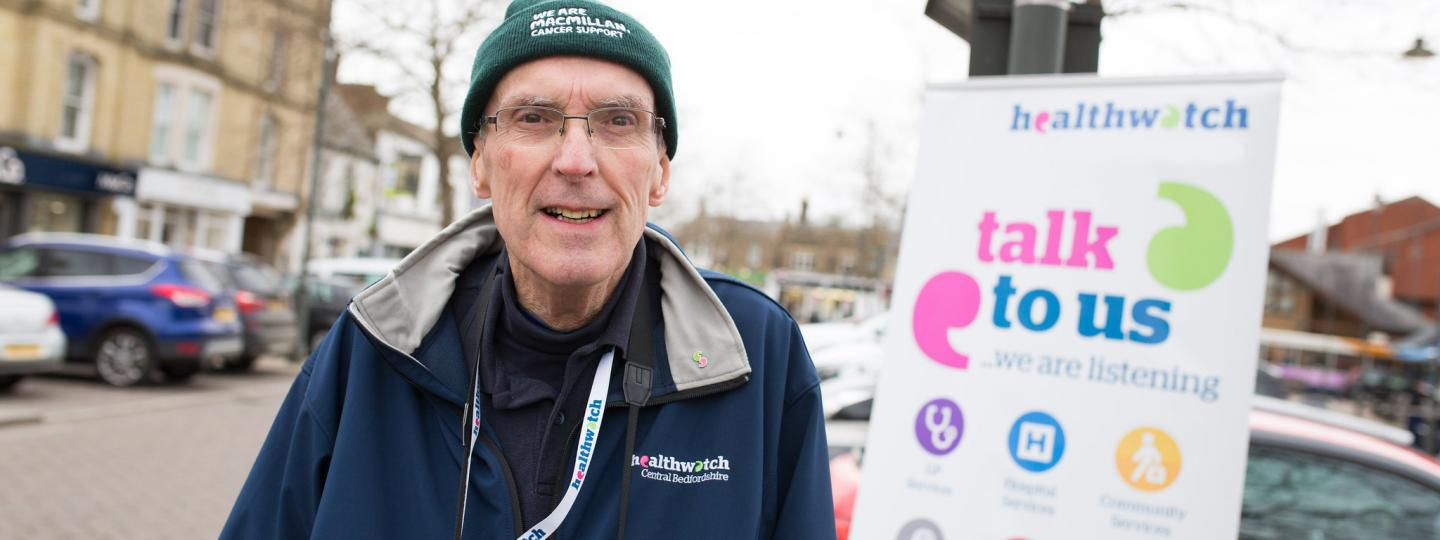 Man standing infront of a Healthwatch branded banner that says 'talk to us'