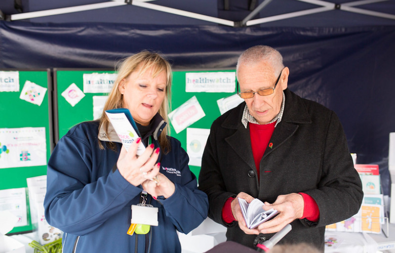 Woman holding a leaflet showing it to a middle age man who is also looking at his own leaflet