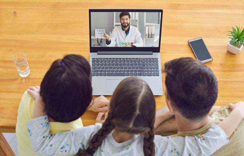 Mother and children talking to doctor via their laptop